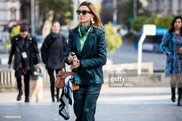 Guest is seen wearing Hermes bag, silk green suit during day 3 of the Mercedes-Benz Tbilisi Fashion Week on November 02, 2019 in Tbilisi, Georgia.
