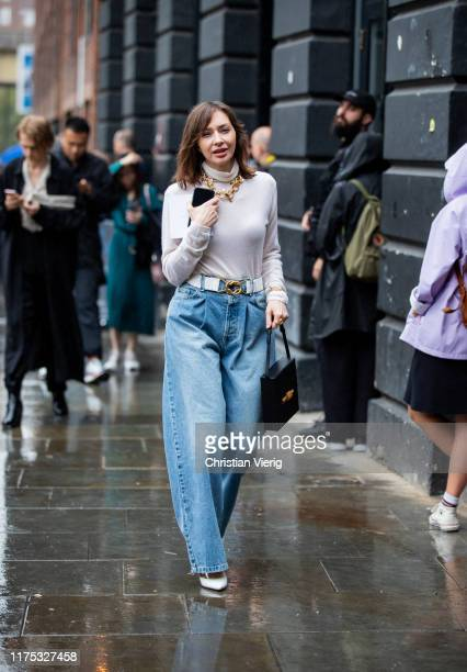 A guest is seen wearing high waist wide leg denim jeans with belt turtleneck necklace outside Christopher Kane during London Fashion Week September...