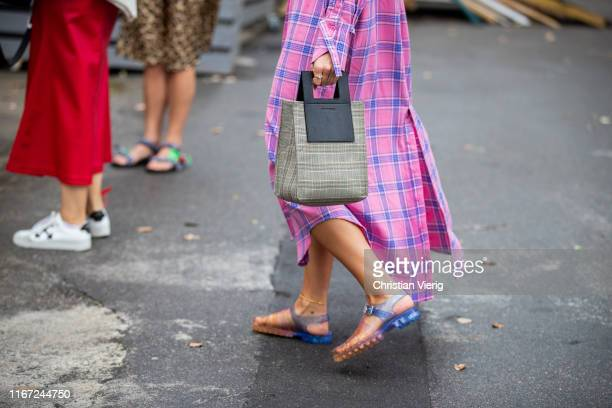 Guest is seen wearing Holzweiler bag, pink plaid button up dress outside Munthe during Copenhagen Fashion Week Spring/Summer 2020 on August 07, 2019...