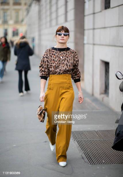 A guest is seen wearing jumper with animal print high waist mustard pants outside Roberto Cavalli on Day 4 Milan Fashion Week Autumn/Winter 2019/20...