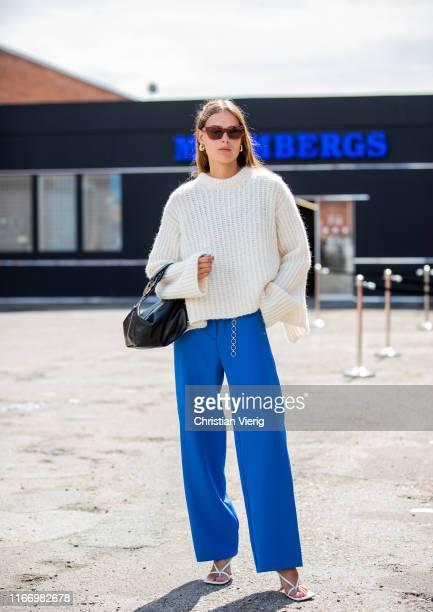 A guest is seen wearing knit blue pants outside By Malene Birger during Copenhagen Fashion Week Spring/Summer 2020 on August 08 2019 in Copenhagen...