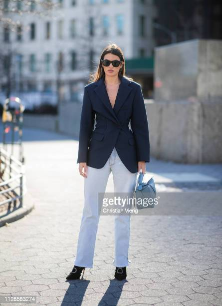 A guest is seen wearing Loewe bag navy blazer jeans outside SelfPortrait during New York Fashion Week Autumn Winter 2019 on February 09 2019 in New...