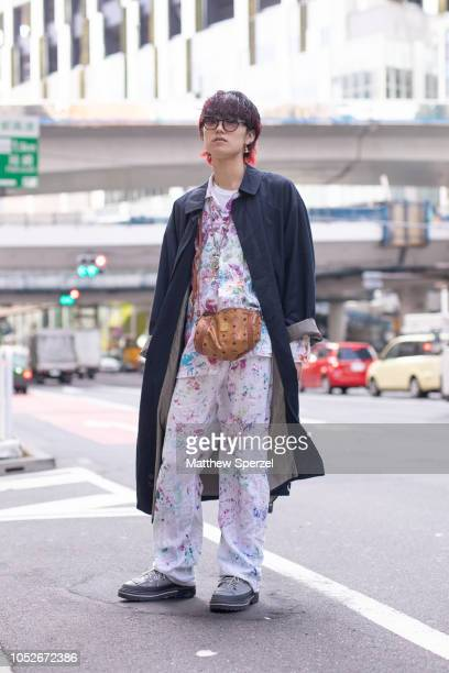 A guest is seen wearing long navy coat paint splatter pattern white jumpsuit brown leather MCM bag with grey sneakers during the Amazon Fashion Week...