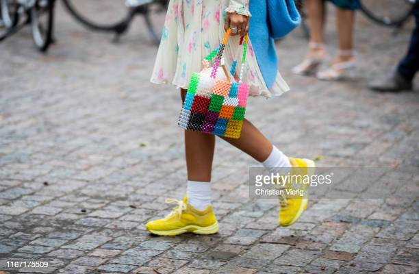 Guest is seen wearing multi colored bag, yellow Chanel sneaker outside Saks Potts during Copenhagen Fashion Week Spring/Summer 2020 on August 08,...