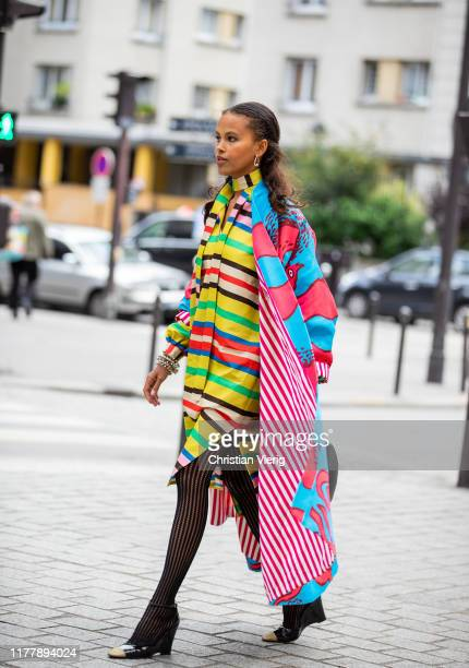 A guest is seen wearing multi colored dress and coat with mixed print outside Issey Miyake during Paris Fashion Week Womenswear Spring Summer 2020 on...