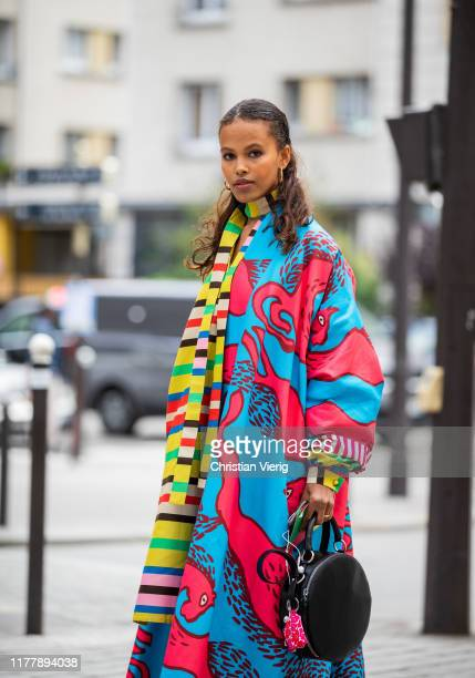 Guest is seen wearing multi colored dress and coat with mixed print outside Issey Miyake during Paris Fashion Week Womenswear Spring Summer 2020 on...