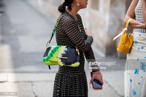 A guest is seen wearing multi colored Prada bag outside M1992 during the Milan Men's Fashion Week Spring/Summer 2020 on June 15 2019 in Milan Italy