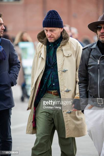 Guest is seen wearing navy beanie, beige trench coat, khaki pants during Pitti Uomo 97 at Fortezza Da Basso on January 07, 2020 in Florence, Italy.