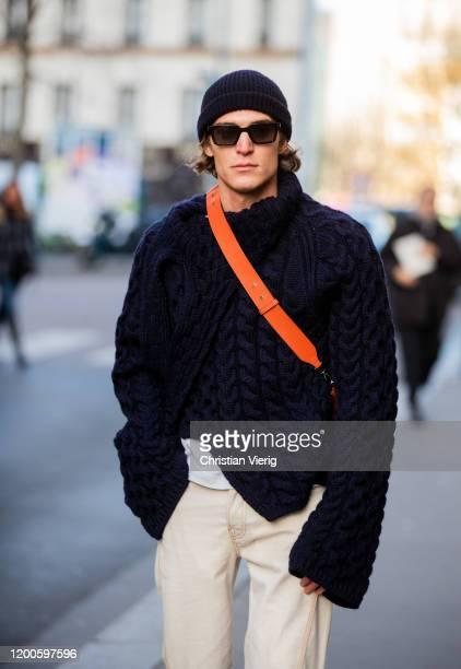 Guest is seen wearing navy knit, orange bag, beanie, creme white pants outside Lanvin during Paris Fashion Week - Menswear F/W 2020-2021 on January...