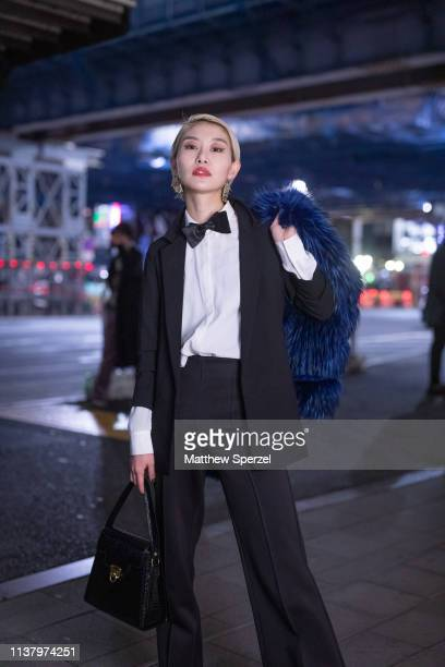 A guest is seen wearing navy shag fur coat black suit white shirt with black bow tie during the Amazon Fashion Week TOKYO 2019 A/W on March 23 2019...