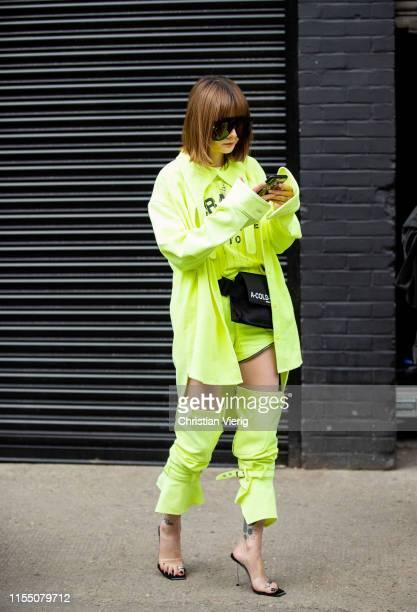 Guest is seen wearing neon jacket, skirt, pants, black A Cold Wall fanny bag outside Xander Zhou during London Fashion Week Men's June 2019 on June...