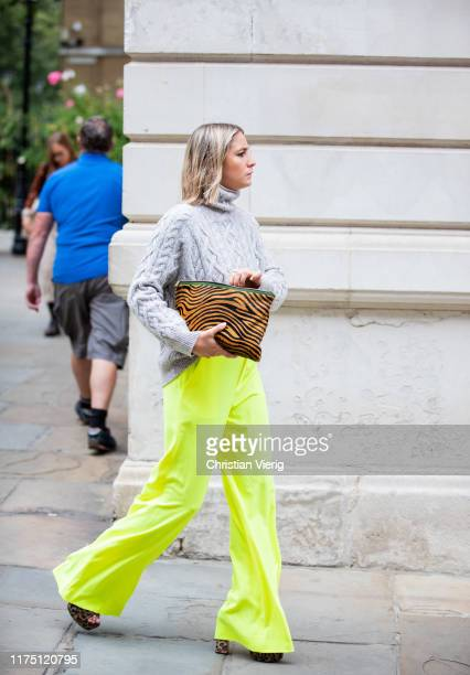 Guest is seen wearing neon pants, knit, clutch with animal print outside Erdem during London Fashion Week September 2019 on September 16, 2019 in...