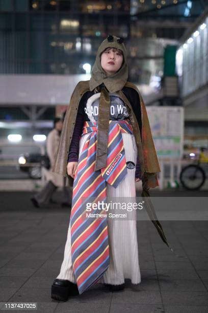 A guest is seen wearing olive green hood and jacket oversized striped neck tie belt white pleated skirt during the Amazon Fashion Week TOKYO 2019 A/W...