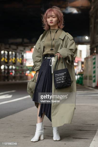 A guest is seen wearing olive green sweater and coat black pleated skirt black bag and white tabi shoes during the Amazon Fashion Week TOKYO 2019 A/W...