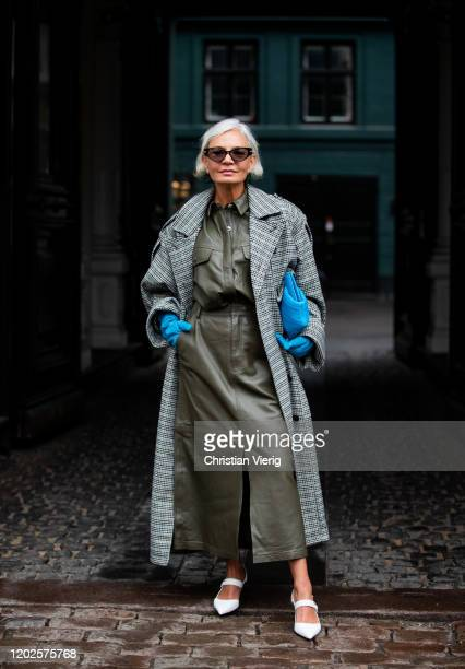 A guest is seen wearing olive skirt button shirt blue gloves and bag grey checkered coat outside Gestuz on Day 1 during Copenhagen Fashion Week...