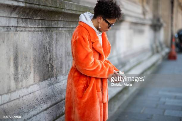 A guest is seen wearing orange coat hoody outside Iris Van Herpen during Paris Fashion Week Haute Couture Spring Summer 2019 on January 21 2019 in...