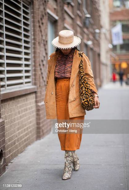 A guest is seen wearing orange cropped pants animal print snake print boots straw hat outside Collina Strada during New York Fashion Week Autumn...