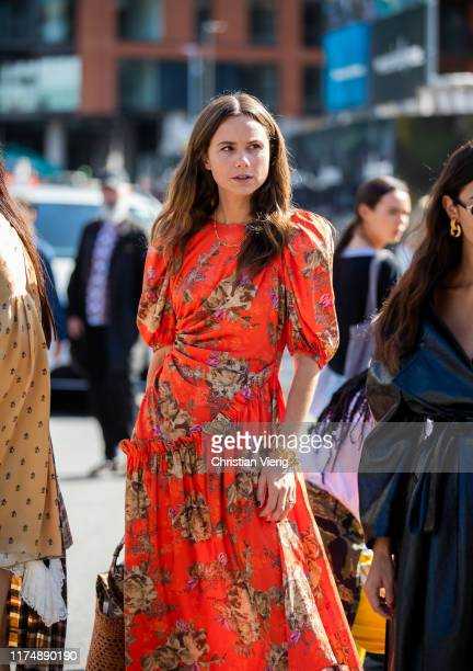 A guest is seen wearing orange dress with floral print outside Preen during London Fashion Week September 2019 on September 15 2019 in London England