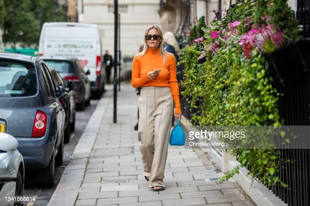 Guest is seen wearing orange jumper, beige pants, blue bag outside Paul & Joe during London Fashion Week September 2021 on September 20, 2021 in...