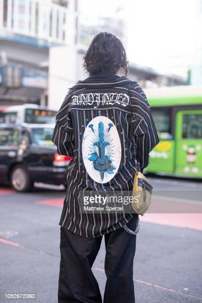 A guest is seen wearing oversized black/white stripe shirt with black pants and silver chain during the Amazon Fashion Week TOKYO 2019 S/S on October...