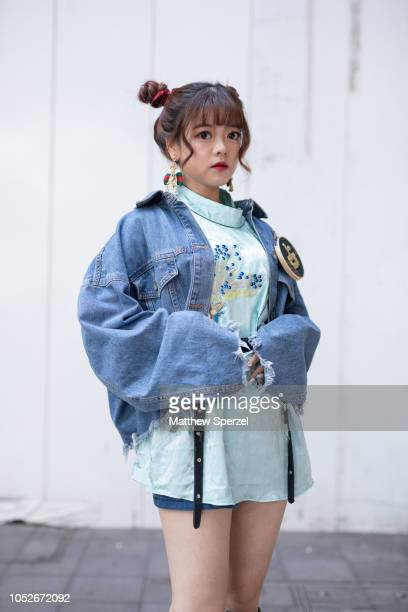 A guest is seen wearing oversized torn denim jacket baby blue dress kneehigh boots during the Amazon Fashion Week TOKYO 2019 S/S on October 20 2018...