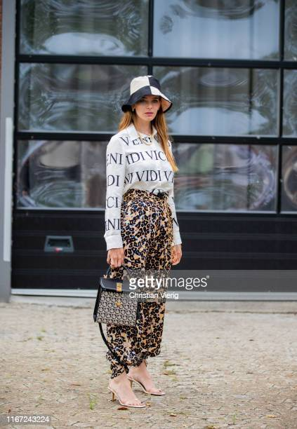 Guest is seen wearing pants with animal print, bucket hat outside Munthe during Copenhagen Fashion Week Spring/Summer 2020 on August 07, 2019 in...