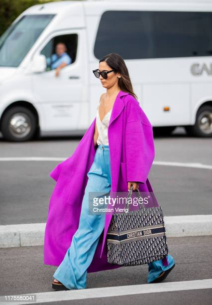 A guest is seen wearing pink coat Dior bag outside the Prada show during Milan Fashion Week Spring/Summer 2020 on September 18 2019 in Milan Italy