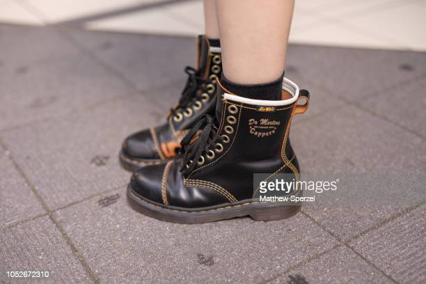 A guest is seen wearing pink dress black leather jacket belt and Dr Martens boots during the Amazon Fashion Week TOKYO 2019 S/S on October 20 2018 in...