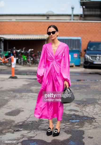 Guest is seen wearing pink dress outside By Malene Birger during Copenhagen Fashion Week Spring/Summer 2020 on August 08, 2019 in Copenhagen, Denmark.