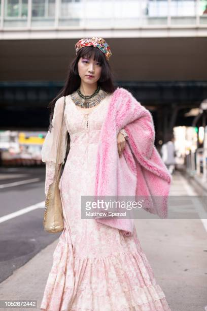 A guest is seen wearing pink fur coat cream dress cadet hat with military pins during the Amazon Fashion Week TOKYO 2019 S/S on October 20 2018 in...