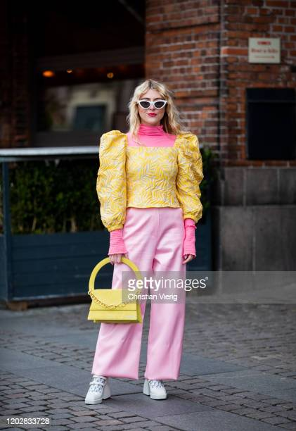 A guest is seen wearing pink pants yellow top and bag outside Helmstedt during Copenhagen Fashion Week Autumn/Winter 2020 Day 2 on January 29 2020 in...