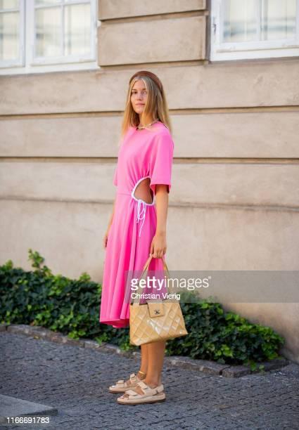 Guest is seen wearing pink ripped dress, beige Chanel bag, sandals outside Helmstedt during Copenhagen Fashion Week Spring/Summer 2020 on August 07,...
