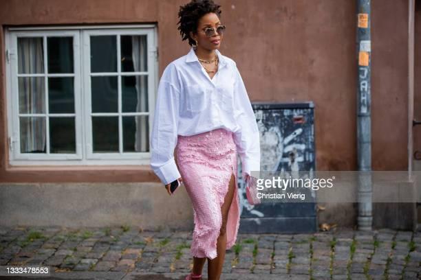 Guest is seen wearing pink skirt, white button shirt outside Lovechild on August 10, 2021 in Copenhagen, Denmark.