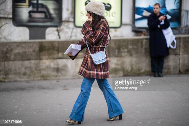 A guest is seen wearing plaid coat flared denim jeans outside Acne during Paris Fashion Week Menswear F/W 20192020 Day Six on January 20 2019 in...