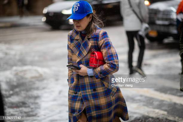 Guest is seen wearing plaid coat outside Coach during New York Fashion Week Autumn Winter 2019 on February 12, 2019 in New York City.