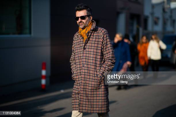 A guest is seen wearing plaid coat outside Gucci on Day 1 Milan Fashion Week Autumn/Winter 2019/20 on February 20 2019 in Milan Italy