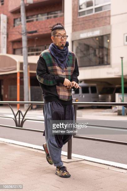 A guest is seen wearing plaid sweater navy scarf black/grey pants and floral pattern sneakers during the Amazon Fashion Week TOKYO 2019 S/S on...