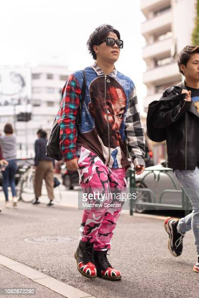 A guest is seen wearing plaid with MLK graphic shirt pink camo pants and union jack boots during the Amazon Fashion Week TOKYO 2019 S/S on October 20...