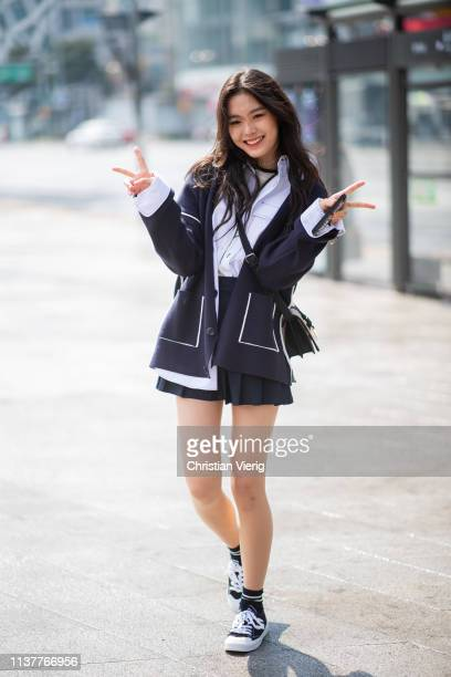 A guest is seen wearing pleated mini skirt showing peace sign at the Hera Seoul Fashion Week 2019 F/W at Dongdaemun Design Plaza at Dongdaemun Design...