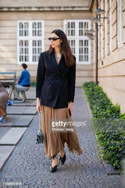 A guest is seen wearing pleated skirt black blazer outside Helmstedt during Copenhagen Fashion Week Spring/Summer 2020 on August 07 2019 in...