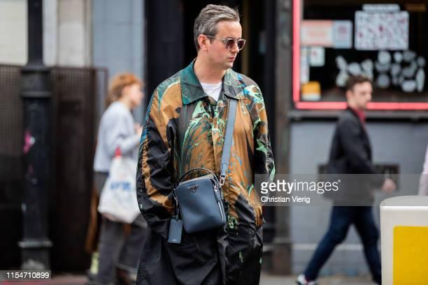 Guest is seen wearing Prada bag, jacket with print outside John Lawrence Sullivan during London Fashion Week Men's June 2019 on June 08, 2019 in...