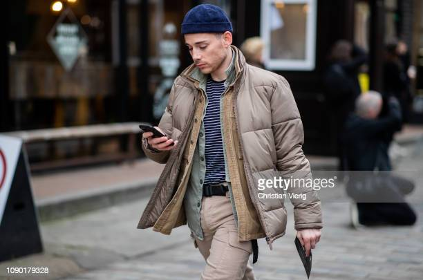 A guest is seen wearing puffer jacket blue beanie during London Fashion Week Men's January 2019 on January 05 2019 in London England