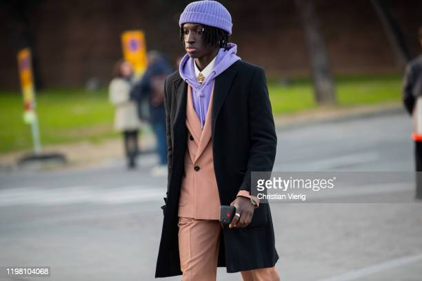 Guest is seen wearing purple beanie, hoody, salmon colored suit, black coat during Pitti Uomo 97 at Fortezza Da Basso on January 07, 2020 in...