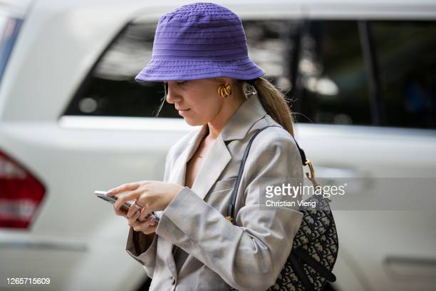 Guest is seen wearing purple bucket hat, checkered blazer and skirt outside Henrik Vibskov during Copenhagen Fashion Week Spring/Summer 2021 on...