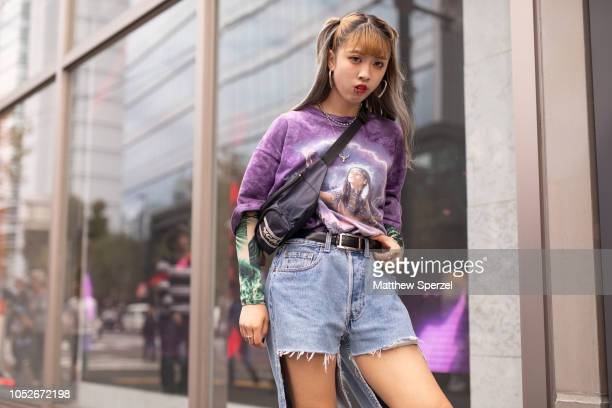 A guest is seen wearing purple graphic print shirt torn denim jeans navy crossbody bag and black boots during the Amazon Fashion Week TOKYO 2019 S/S...