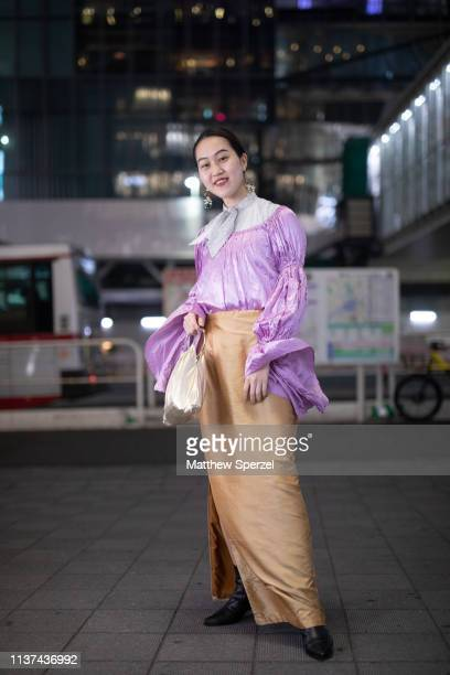 A guest is seen wearing purple shirt grey scarf silver bag tan skirt during the Amazon Fashion Week TOKYO 2019 A/W on March 21 2019 in Tokyo Japan