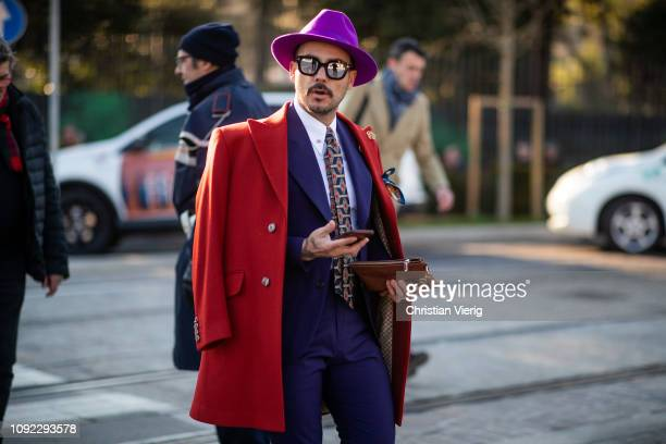 A guest is seen wearing purple suit red wool coat hat during the 95th Pitti Uomo at Fortezza Da Basso on January 10 2019 in Florence Italy