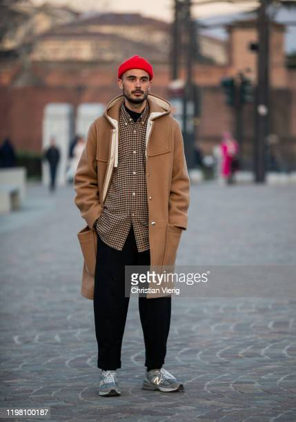 A guest is seen wearing red beanie brown jacket during Pitti Uomo 97 at Fortezza Da Basso on January 07 2020 in Florence Italy