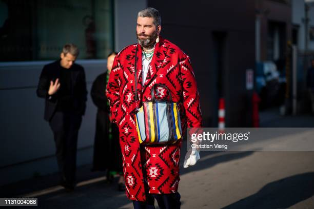 A guest is seen wearing red coat with print striped Balenciaga bag outside Gucci on Day 1 Milan Fashion Week Autumn/Winter 2019/20 on February 20...