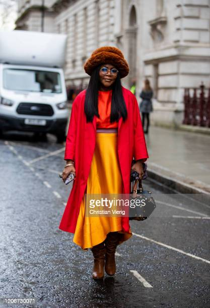 Guest is seen wearing red cropped top, coat, yellow silk skirt, hat outside Roksanda during London Fashion Week February 2020 on February 16, 2020 in...